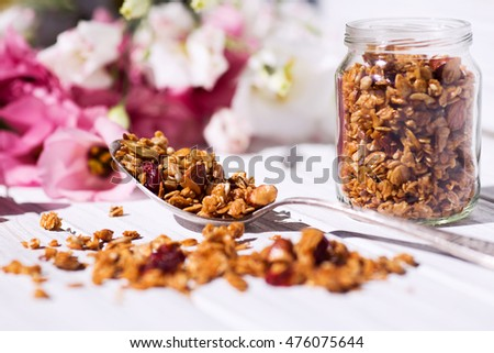 granola in a spoon and a pot standing on a wooden table on a background of flowers