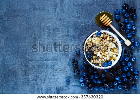 Granola in vintage mug, dark berries and honey for delicious breakfast on grunge background with space for text on left, top view. Organic healthy food and diet concept. - stock photo