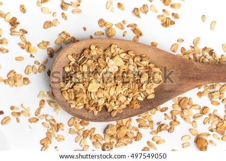 Granola into a spoon isolated on white background