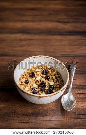 Granola or muesli with oats, fresh berries and nuts in a bowl with a spoon, selective focus - stock photo