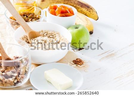 Granola preparation - ingredients, white wood background - stock photo