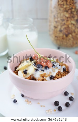 Granola with bananas and fresh berries in a ceramic bowl and homemade yogurt in glass - stock photo