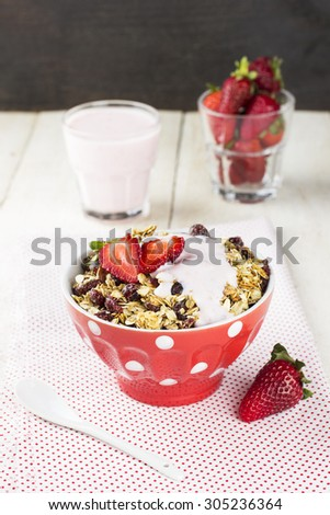 Granola with strawberry and yogurt on a white wooden background