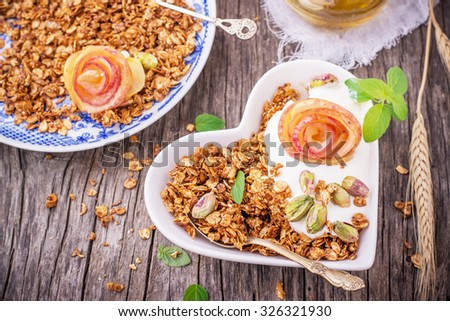 Granola with yogurt and caramel apple slices folded in the shape of a rose bud in a white plate in the shape of a heart on a wooden background. Top view. Gorizonal. selective Focus - stock photo