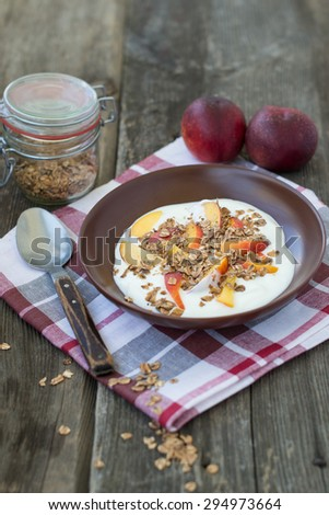 Granola with yogurt and nectarines served for breakfast in a clay brown bowl on wooden background - stock photo
