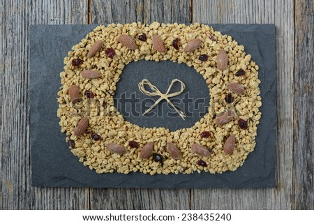 Granola Wreath with Anise, Almonds, and dried Cranberries on Slate and Dark Wood Background - stock photo