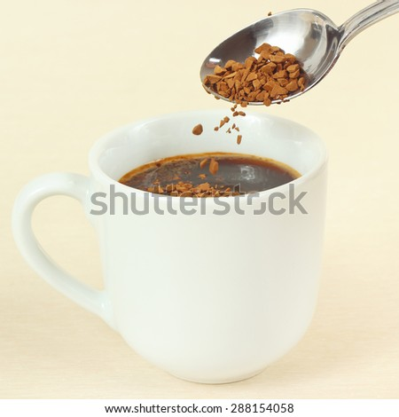 Granulated coffee is poured from a spoon in a cup - stock photo