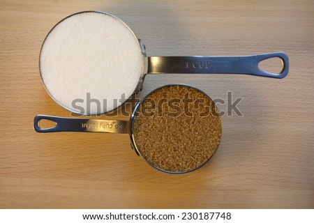 Granulated Sugar and Brown Sugar in Metal Measuring Cup on Wood Background - stock photo
