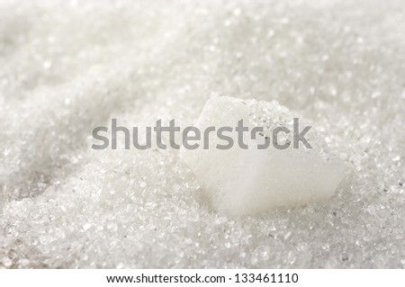 Granulated sugar and sugar cube as background. - stock photo