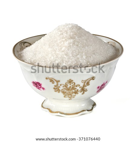 Granulated sugar in antique bowl on white background - stock photo