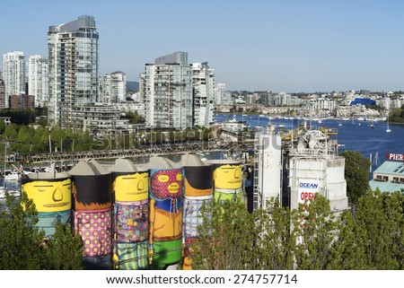 GRANVILLE ISLAND-MAY 2, 2015: Vancouver's oldest industry part Granville Island  changed in last years into famous shopping centre, except few companies. In the background is False Creek and Yaletown - stock photo