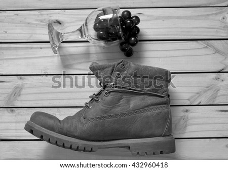 grape and glass and boots on wood back ground.effcet back and wh