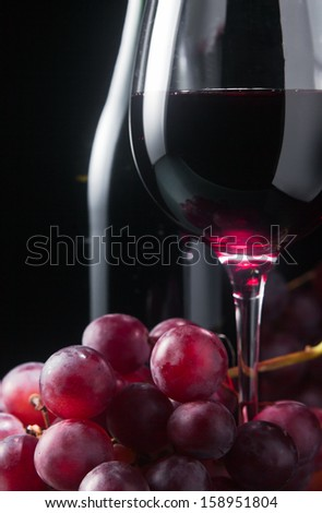 grape and glass with red wine on a black background