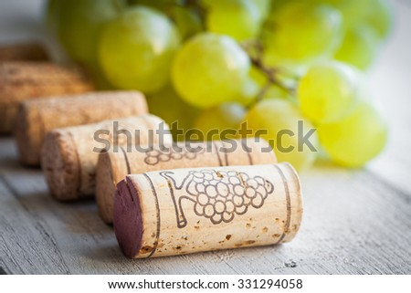 Grape and wine corks on wooden background - stock photo
