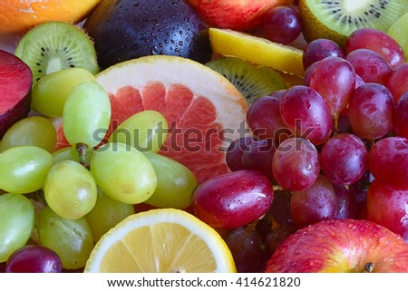 Grape, apple, kiwi and other fruits close-up. Fruit slices. Fruit set. Red fruits. Green fruits, yellow fruits. Fresh fruits. Drops of water on the fruit. - stock photo