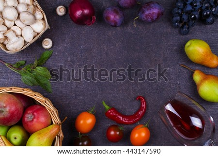 Grape, apples, pears, mushrooms, chili peppers, tomatoes, basil, red onions and glass of red wine on a wooden dark background. View from above, top studio shot of vegetables and fruits  - stock photo