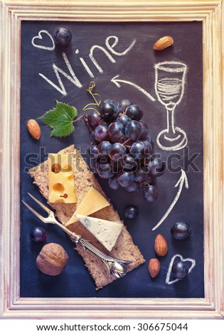Grape cheese wine chalk board. Delicious food ingredients for picnic. Vintage style. Toned photo. - stock photo