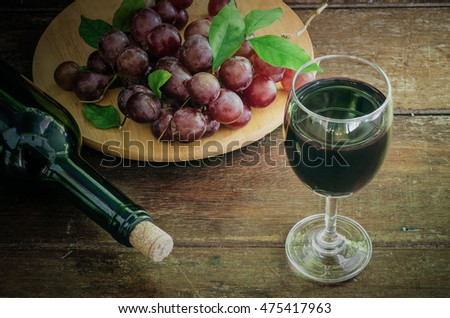 grape fruit wine, still life of glass of fruit wine and bottle on wood