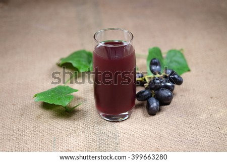 Grape juice and grape on grunge sack fabric background. - stock photo