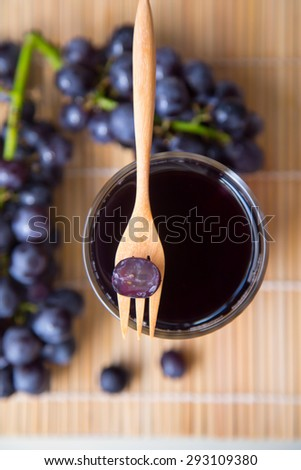 Grape juice in glass and grape fruits on wooden table - stock photo