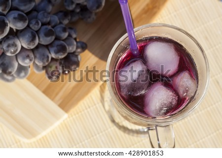 Grape juice with ice in glass and cluster of fresh blue grapes on a wooden table close-up, selective focus