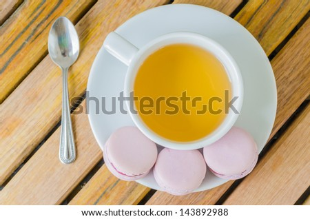 Grape macaroon with white tea cup on the wood table