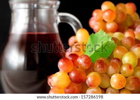 Grape's bunch and a jar of wine on black background - stock photo