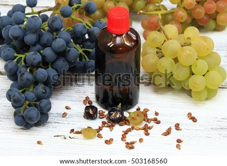 Grape seed oil , grape seeds in front, fresh grapes around