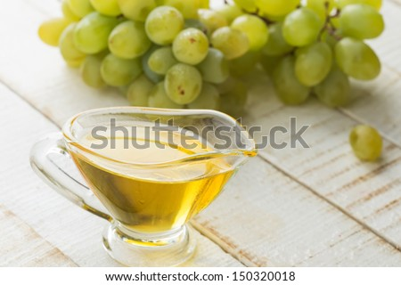 Grape seed oil  on white wooden background. Selective focus. Bio/organic/eco products.