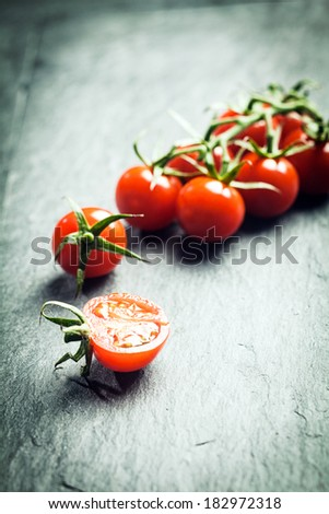 Grape tomatoes on the vine with a single halved tomato in the foreground on a textured surface with highlight and copyspace and shallow dof - stock photo