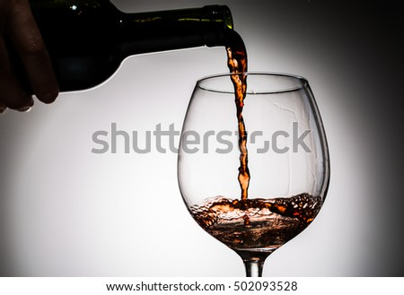 Grape wine poured from bottle into wine glass from glass on blank background