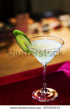 grapefruit and cucumber martini cocktail drink in bar at night - stock photo