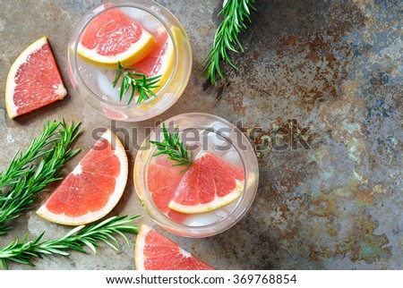 Grapefruit and rosemary drink, alcohol or non-alcohol cocktail or infused water with ice - stock photo
