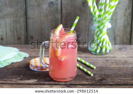 Grapefruit juice in a glass jar with pieces of fruit on a wooden table, selective focus - stock photo