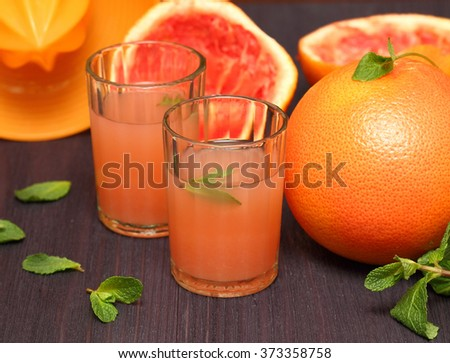 Grapefruit juice on a rustic wooden table.