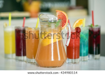 Grapefruit lemonade in jag and colorful beverages in glass  - stock photo