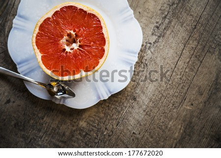 Grapefruit on a white plate on a wood background with spoon - stock photo