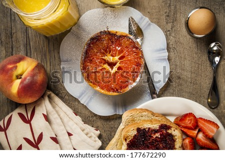 Grapefruit on a white plate on a wood background with spoon, orange juice, napkin, toast, soft boiled egg, toast, strawberries, and a peach - stock photo