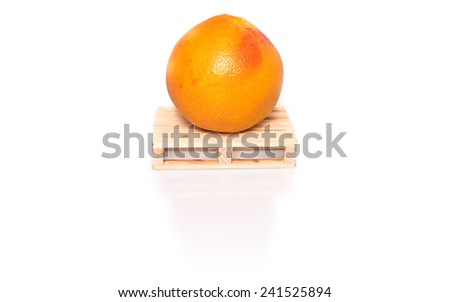 grapefruit on wood pallet ready for shipment - conceptual photo with shadow and reflection on white background - stock photo