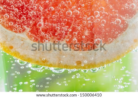 Grapefruit slice in carbonated water with a lot of bubbles