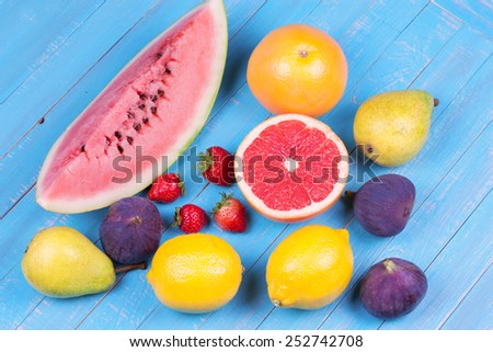 Grapefruits, pears, lemons, watermelon, figs, strawberry, pomelo and mint on wooden background; still life with fruits - stock photo