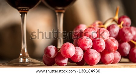 grapes and a cup of wine over a wooden table. - stock photo