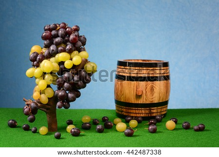 Grapes and wooden barrel for wine on the table - stock photo