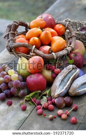 Grapes, apples, pears and tomatoes on a table. - stock photo