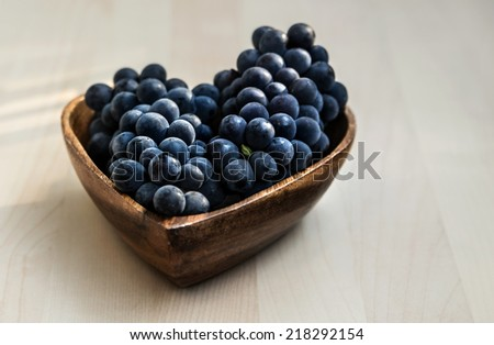 Grapes in a heart shape wooden plate in a natural light from the window, close up - stock photo