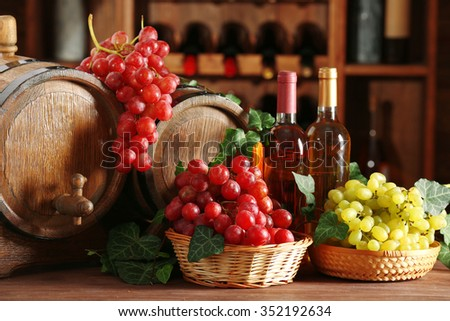 Grapes in bowls and barrel on wooden table - stock photo