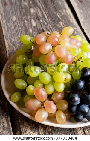 Grapes on a plate on a old wooden table. vertical, close up, top view - stock photo