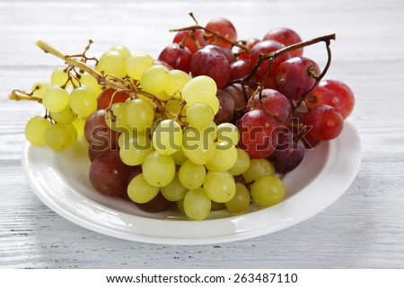 Grapes on a white plate, food closeup - stock photo
