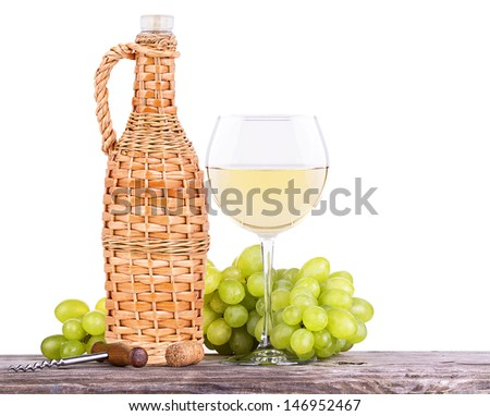 grapes on a wooden vintage table with corkscrew and wine glass isolated on a white background