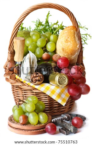 Grapes, wine, nuts, cheese and ciabatta in a wicker basket.